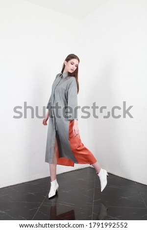 Side view of a model which is turning around to look at her side. Tall slender caucasian brunette model wearing long loose clothes, walking indoors. Studio photography, white walls background