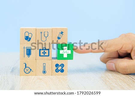 Hand choose medical icon on cube wooden toy blocks stack in with other medical symbols concepts of illness treatment and health safety insurance.