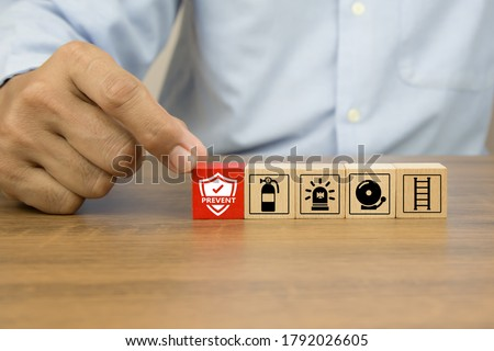 Close-up hand choose prevent icon on cube wooden toy blocks stacked with fire exit prevention icon for fire safety protection concepts. Royalty-Free Stock Photo #1792026605