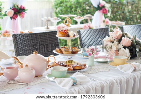 Pastel high tea set up featuring pastel pink, blue, yellow and green Royal Doulton tea set and an assortment of cupcakes, sweets and pastries. Royalty-Free Stock Photo #1792303606