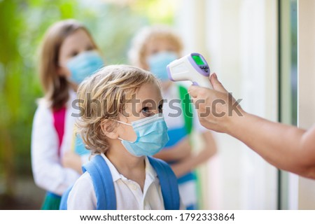 Temperature screening and medical check at school. Child in face mask in class in covid-19 outbreak. Teacher with thermometer at preschool entrance. Social distancing. Coronavirus prevention. #1792333864