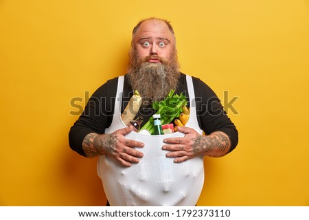 Bothered surprised bearded man stocks up on products, eats too much junk food, has good appetite, suffers from gluttony, cannot control his nutrition, should lose weight, looks sadly at camera