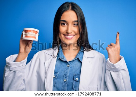 Young beautiful brunette dentist woman wearing coat holding plastic teeth prosthesis surprised with an idea or question pointing finger with happy face, number one