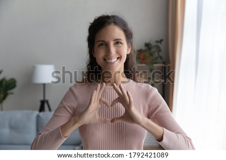 Headshot portrait of smiling young Caucasian woman show heart sign symbol with hands feel grateful thankful, profile picture of happy millennial female demonstrate love and support, volunteer concept