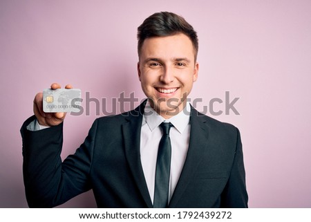 Young handsome caucasian business man holding finance credit card over pink background with a happy face standing and smiling with a confident smile showing teeth