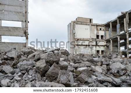 Concrete debris with rebar against the background of a destroyed building and a gray sky. The concept of recycling industrial buildings. Background. Royalty-Free Stock Photo #1792451608