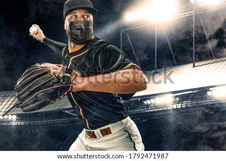 Porfessional baseball player in medical mask. Baseball game in 2020 - time of coronavirus pandemic. Ballplayer on stadium in action. Royalty-Free Stock Photo #1792471987