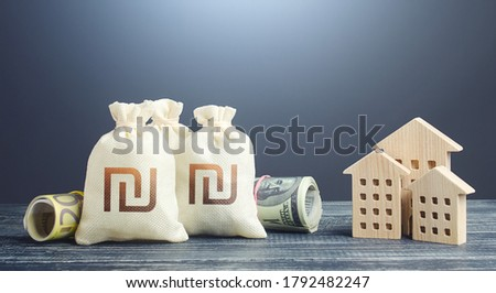 Israeli shekel money bags and residential buildings figures. Financing the construction of new settlements. Municipal budget management. Investments in real estate. Mortgage loan. Taxes. Royalty-Free Stock Photo #1792482247