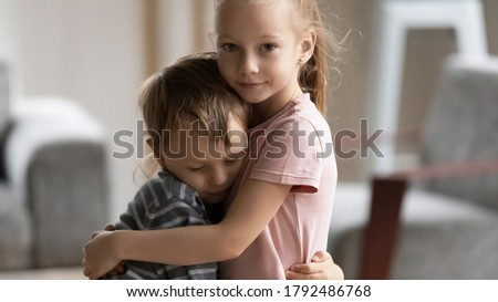 Head shot portrait of little kid girl cuddling smaller brother at home, showing love and care. Compassionate sister comforting soothing upset stressed boy in living room, siblings relations concept.
