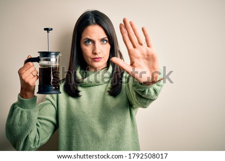 Young woman with blue eyes making cafe using coffe maker standing over white background with open hand doing stop sign with serious and confident expression, defense gesture