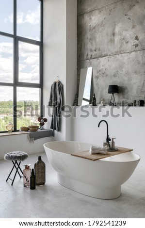 Vertical and side view photo of modern house with contemporary interior in white bathroom with comfortable bathtub, home decor and fresh towels at wooden table #1792541239