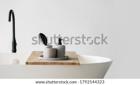 Modern bathroom interior with bathtub and water tap. Panoramic view of tray with hairbrush, soap in bottle dispenser and clean towels at wooden shelf on white contemporary bath near black faucet