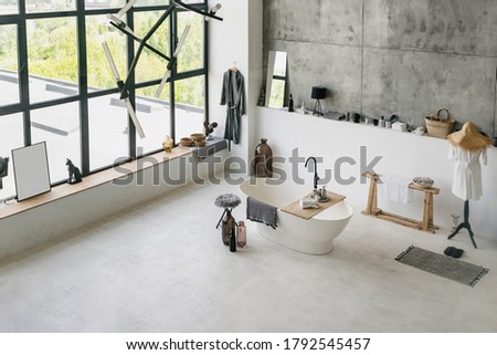 High angle view of modern interior at contemporary bathroom, folded clean towels on wooden shelf at empty bath near cotton bathrobe and house decor with copy space on concrete floor Royalty-Free Stock Photo #1792545457
