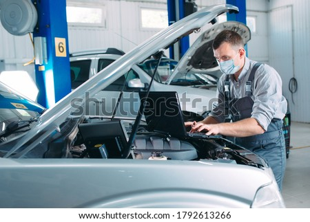 car mechanic using a computer laptop to diagnosing and checking up on car engines parts for fixing and repair Royalty-Free Stock Photo #1792613266