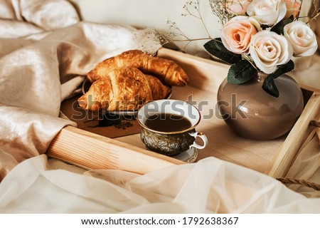 The atmosphere of a romantic morning, coffee in bed. Flowers in a vase, french croissants and a cup of coffee on a wooden tray on a silk bed. Home interior. Lifestyle Royalty-Free Stock Photo #1792638367