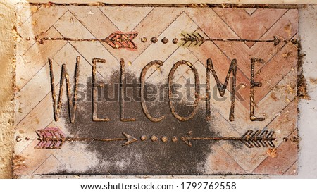 welcome foot print mat on the porch