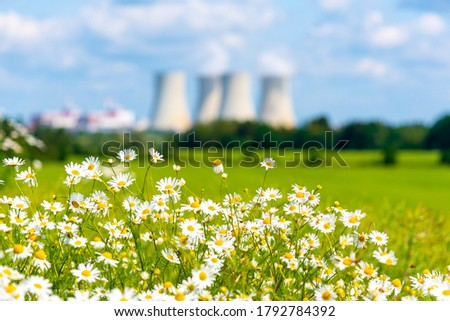 Nuclear power plant out of focus on the background of beautiful green and blooming summer meadow. Temelin, Czech Republic. Royalty-Free Stock Photo #1792784392
