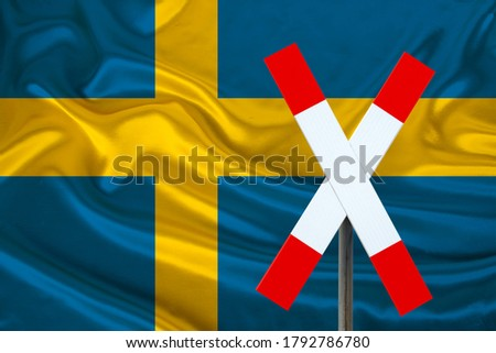 customs sign, stop, attention on the background of the silk national flag of Sweden, the concept of border and customs control, violation of the state border, tourism restrictions