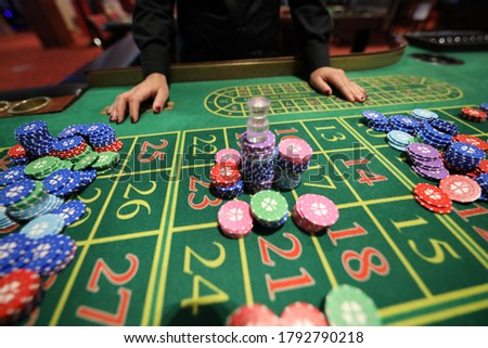 Picture of a green table and betting with chips. Artiste :