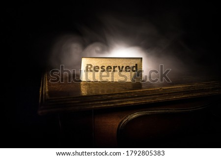 Reserved sign on the table. A tag of reservation placed on the wood table. Metal tag with reservation on dark. Reserved table in a restaurant. Creative concept with colorful lights. Selective focus #1792805383