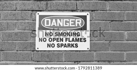 Danger sign posted against brick wall