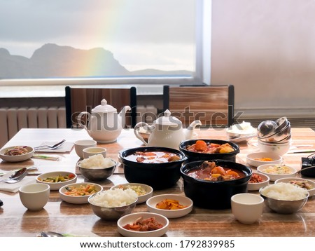 Big meal of korean food for family group for eat and share together in restaurant on light wooden table with blur rainbow and mountain outdoor background. concept of friendship on the table. Royalty-Free Stock Photo #1792839985