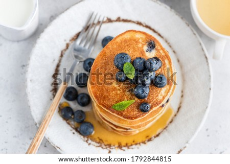 Pancakes with bluberries and sweet maple syrup on a plate. Top view