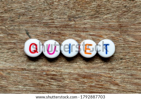 White bead with color letter in word quiet on wood background
