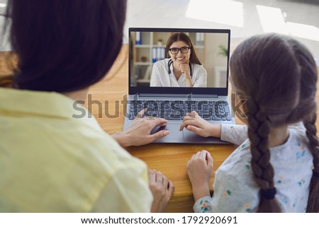 Family doctor online. Mother and child listen to doctor using video chat and have laptop internet connection at home.