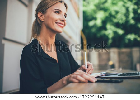 Happy female student with cute smile on face studying information notes learning at outdoors table desktop, cheerful Caucasian woman 20 years old enjoying accounting with education textbook Royalty-Free Stock Photo #1792951147