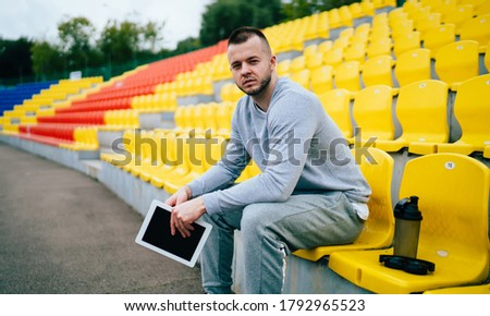 Focused tired young bearded man runner in tracksuit sitting on stadium tribunes with tablet and water bottle and looking at camera Royalty-Free Stock Photo #1792965523