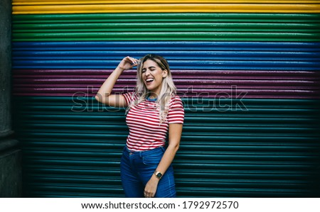 Trendy adolescent teenager dressed in casual apparel smiling and laughing at colorful promotional background, happy Hispanic hipster girl 20 years old rejoicing near copy space publicity area in city Royalty-Free Stock Photo #1792972570