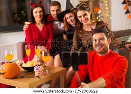 friendship, holiday and people concept - group of happy smiling friends in halloween costumes of vampire, devil, witch and cheetah taking picture by smartphone selfie stick at home party at night