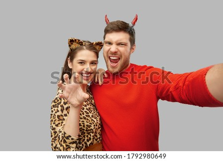 holiday and people concept - happy couple in halloween costumes of devil and leopard taking selfie over grey background