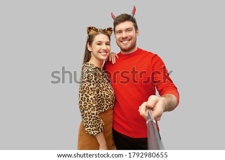 holiday and people concept - happy smiling couple in halloween costumes of devil and leopard taking picture by selfie stick over grey background