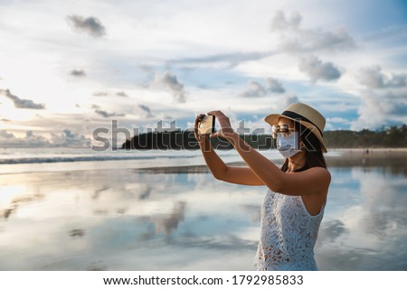 New normal travel concept, Happy traveler asian woman with mask and mobile phone sightseeing in Kata beach, Phuket, Thailand Royalty-Free Stock Photo #1792985833