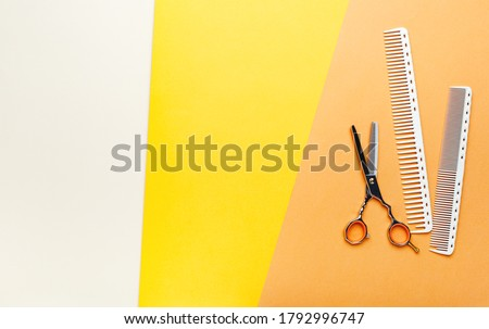Hair Brush comb scissors. Hairdresser tools, hair salon equipment for professional hairdressing in beauty salon, haircut service barber shop. Top view on color orange background Copy space Royalty-Free Stock Photo #1792996747