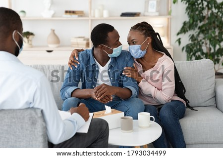 Saved Marriage. Happy Black Couple In Medical Masks Embracing At Councelor's Office After Successful Marital Therapy #1793034499