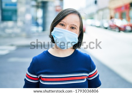 Beautiful brunette woman with down syndrome at the town on a sunny day wearing safety medical mask for coronavirus Royalty-Free Stock Photo #1793036806