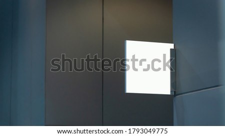 Blank transparent sign plate design mockup mock up on the wall near office entrance interior. Signage panel door number template. Clear printing board for logo branding.