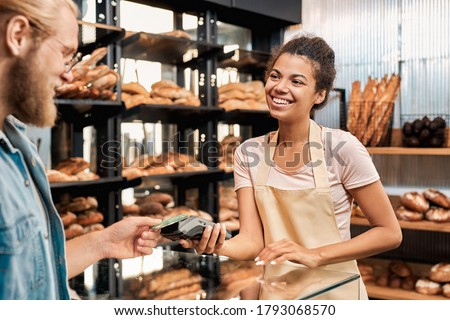 Young adult female working in bakery shop, taking wireless payment from client while he using contactless credit card in store