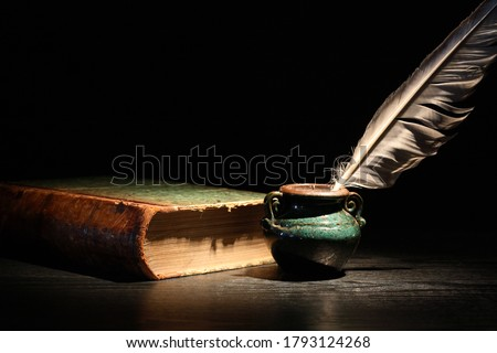 Vintage still life with old book and quill pen on dark background Royalty-Free Stock Photo #1793124268