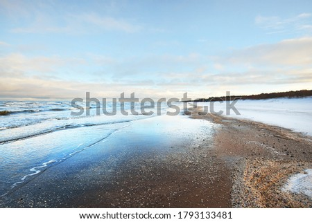 A view from the snow-covered sandy Baltic sea shore at sunset. Riga bay, Latvia. Dramatic sky. Crystal clear blue water. Fickle weather, waves and water splashes. Winter tourism, global warming theme #1793133481