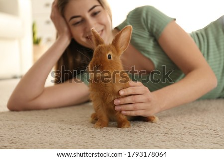 Young woman with adorable rabbit on floor indoors. Lovely pet