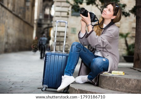 Young cheerful woman looking curious and taking a pictures outdoors