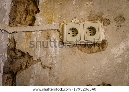 Old brick wall with destroyed plaster in vintage living room. Distressed Texture wallpaper backdrop. Old electrical outlet power socket