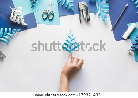 How to make paper beautiful Christmas toy snowflake to decorate room with children. Step by step instructions. Hands making winter DIY. Step 8. Glug following strips on other side. Alternate sides.