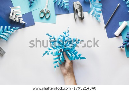 How to make paper beautiful Christmas toy snowflake to decorate room with children at home. Step by step instructions. Top view. Hands making DIY winter craft project. Step 11. Enjoy ready toy