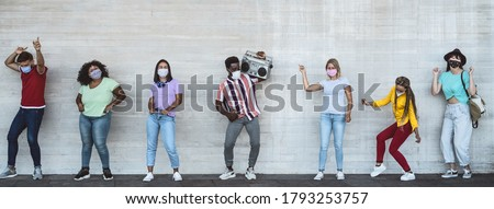 Happy friends wearing face mask listening music with vintage boombox outdoor - Multiracial young people having fun dancing together during corona virus outbreak - Youth millennial friendship concept #1793253757
