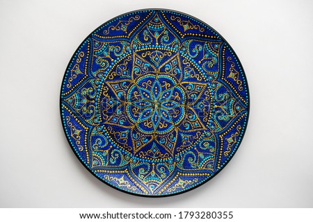Decorative ceramic plate with black, blue and golden colors, painted plate on white background, closeup, top view. Decorative porcelain plate painted with acrylic paints, handwork, dot painting Royalty-Free Stock Photo #1793280355